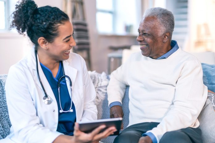 a doctor and her patient are smiling at each other and looking at a digital tablet together in a healthcare setting